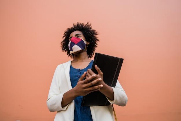 保護マスクを着用し、通りで屋外に立っている間クリップボードを保持しているアフロ実業家の肖像画