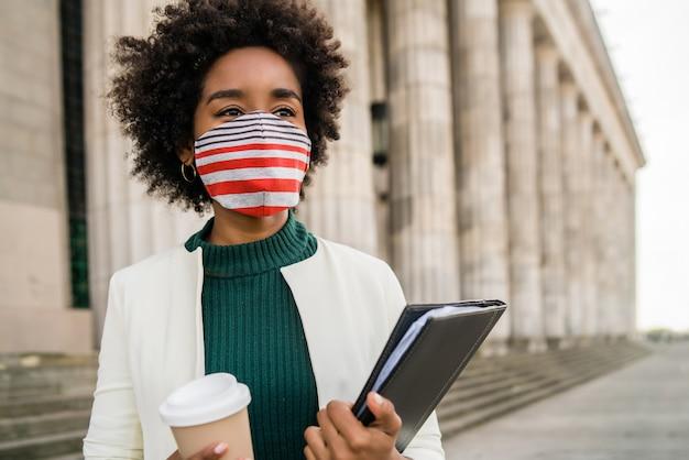 通りで屋外に立っている間コーヒーとクリップボードのカップを保持している保護マスクを持つアフロ実業家の肖像画。ビジネスコンセプト。