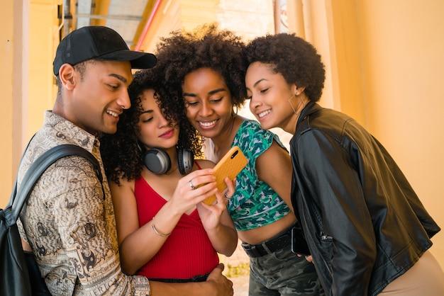 街で楽しんで、携帯電話を使用しながら一緒に楽しい時間を過ごしているアフロの友人の肖像画。友情とライフスタイルのコンセプト。