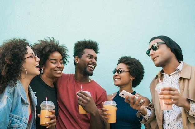 Портрет афро-друзей, весело проводящих время вместе и хорошо проводящих время, попивая свежий фруктовый сок.