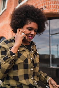 通りで屋外の電話で話しているアフロのラテン女性の肖像画。都市とコミュニケーションの概念。
