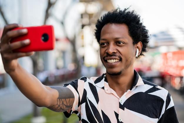 Портрет афро-человека, делающего селфи с телефоном на открытом воздухе на улице.