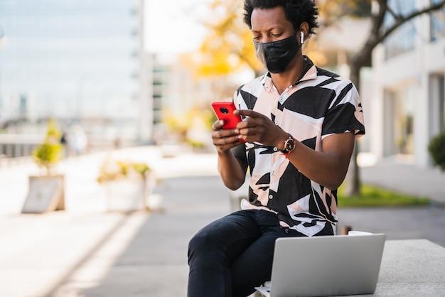 通りを屋外で歩いているときに彼の携帯電話を使用してアフロマンの肖像画。新しい通常のライフスタイルのコンセプト。