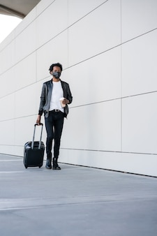 スーツケースを持って、通りを屋外で歩きながらコーヒーを持っているアフロの観光客の男性の肖像画。観光の概念。