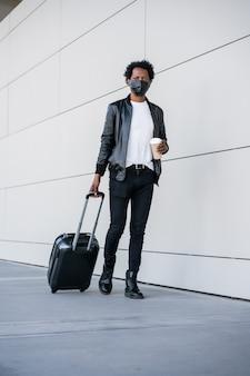 가방을 들고 거리에 야외에서 걷는 동안 커피 한 잔을 들고 아프리카 관광 남자의 초상화. 관광 개념.