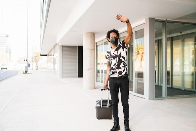 スーツケースを持って、通りを屋外で歩きながらタクシーを呼ぶために手を上げるアフロの観光客の男性の肖像画。観光の概念。