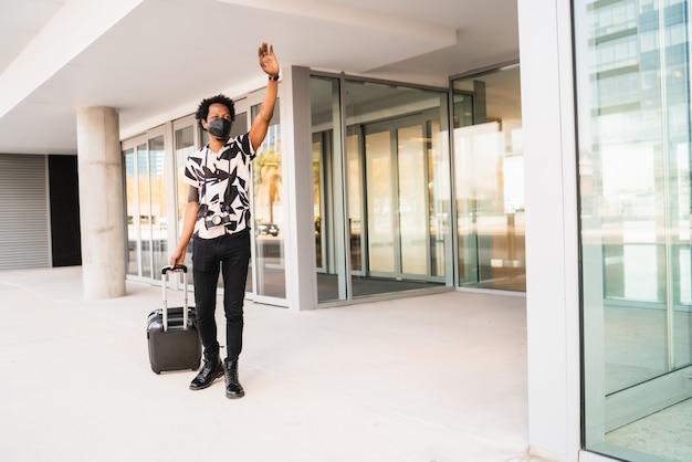 スーツケースを持って、通りを屋外で歩きながらタクシーを呼ぶために手を上げるアフロの観光客の肖像画。観光の概念。