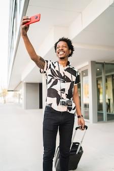 スーツケースを持って、路上で屋外の電話で自分撮りをしているアフロの観光客の男性の肖像画。観光の概念。