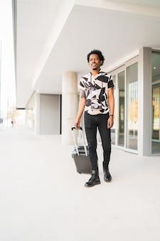 通りを屋外で歩きながらスーツケースを運ぶアフロ観光男性の肖像画。観光の概念。