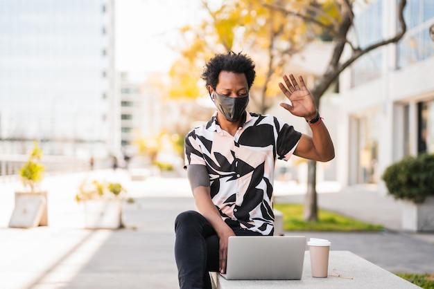 屋外に座っている間彼のラップトップでビデオ通話をしているアフロ観光客の男の肖像画。新しい通常のライフスタイルのコンセプト。