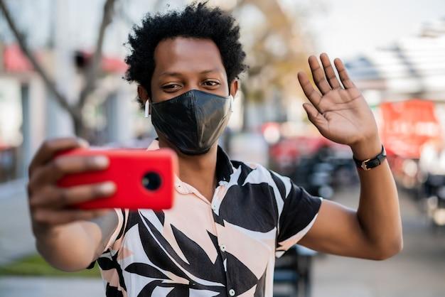야외 거리에 서있는 동안 휴대 전화에 화상 통화를 하 고 아프리카 관광 남자의 초상화. 새로운 정상적인 생활 개념. 관광 개념.