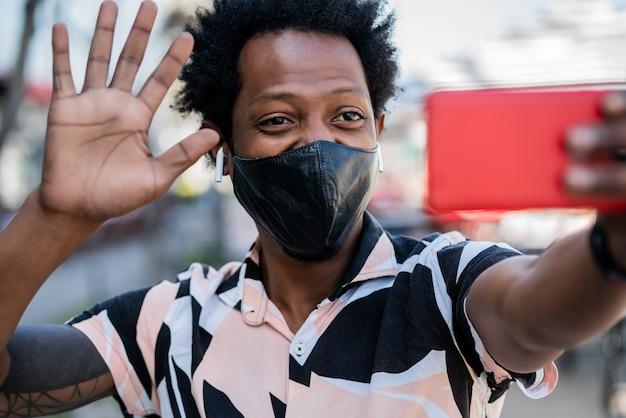 路上で屋外に立っているときに携帯電話でビデオ通話をしているアフロ観光男性の肖像画。新しい通常の生活の概念。観光の概念。