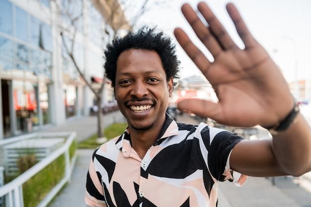 路上で屋外に立っているときに手でこんにちはと言っているアフロ観光男性の肖像画