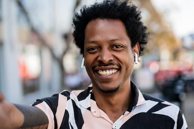 Портрет афро-туристического человека, делающего селфи, стоя на улице на улице. концепция городского и образа жизни.