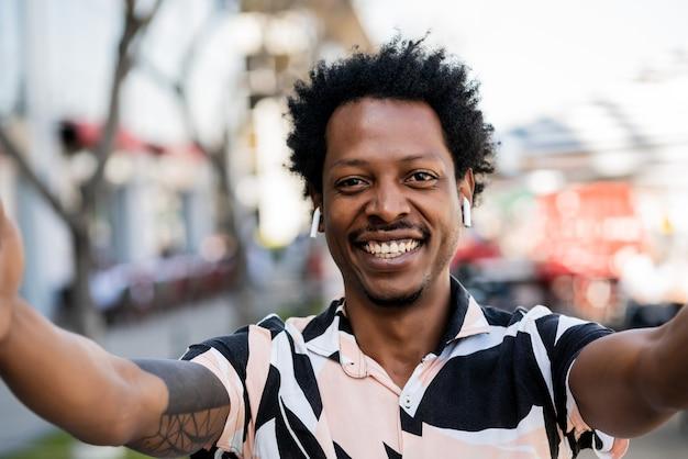 Портрет афро-туриста, делающего селфи, стоя на улице на улице