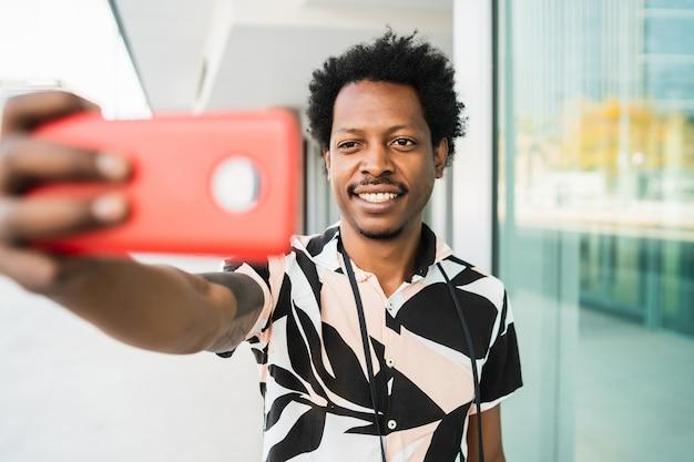 Портрет афро-туристического человека, делающего селфи с телефоном на открытом воздухе на улице. концепция туризма.