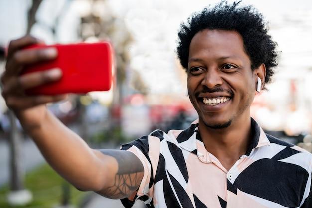 Портрет афро-туристического человека, делающего селфи с телефоном на открытом воздухе на улице.