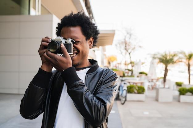 通りを屋外で歩きながらカメラで写真を撮るアフロ観光男性の肖像画。観光の概念。
