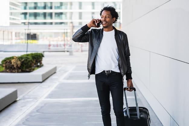 電話で話し、通りを屋外で歩きながらスーツケースを運ぶアフロ観光男性の肖像画