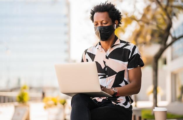 Портрет афро-туриста, сидящего на открытом воздухе и использующего свой ноутбук в защитной маске