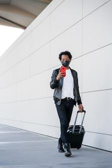 彼の携帯電話を使用し、屋外を歩きながらスーツケースを運ぶアフロの観光客の男性の肖像画。観光の概念。新しい通常のライフスタイルのコンセプト。