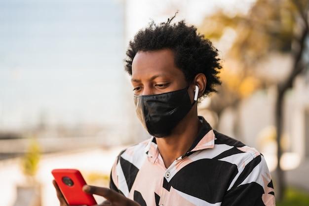 通りを屋外で歩いているときに彼の携帯電話を使用してアフロ観光男性の肖像画。新しい通常のライフスタイルのコンセプト。観光の概念。