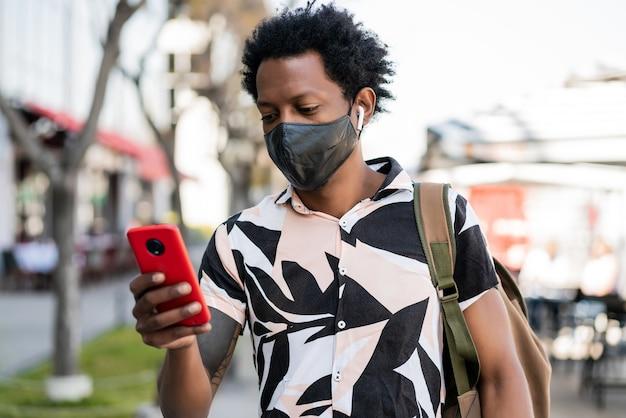거리에 야외에서 걷는 동안 자신의 휴대 전화를 사용하는 아프리카 관광 남자의 초상화. 새로운 정상적인 라이프 스타일 개념. 관광 개념.