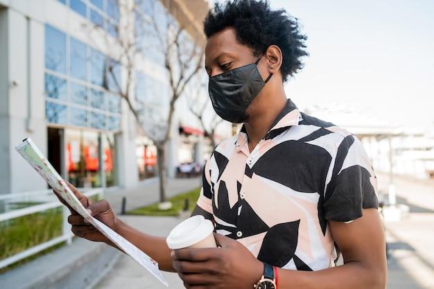 保護マスクを着用し、通りを屋外で歩きながら地図上で道順を探しているアフロの観光客の男性の肖像画。観光の概念。