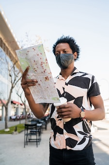 보호 마스크를 착용 하 고 거리에 야외에서 걷는 동안지도에 방향을 찾고 아프리카 관광 남자의 초상화. 관광 개념.