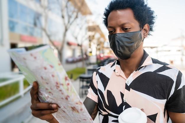Портрет афро-туристического человека в защитной маске, ищущего направления на карте во время прогулки по улице. концепция туризма.