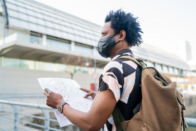 保護マスクを着用し、地図上で道順を探しているアフロ観光男性の肖像画