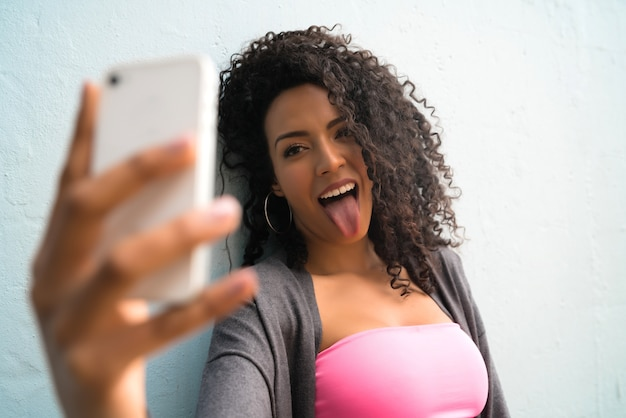 회색 벽에 그녀의 mophile 전화 셀카를 복용 아프리카 여자의 초상화. 기술 개념.