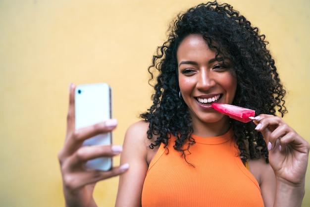 アイスクリームを食べながら彼女のmophile電話でselfiesを取っているアフロ女性の肖像画。テクノロジーとライフスタイルのコンセプト。