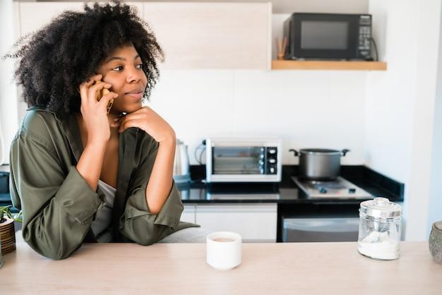 Портрет афро-женщины разговаривает по телефону с чашкой кофе дома