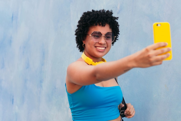 거리에서 산책 하 고 그녀의 휴대 전화로 selfie를 복용 아프리카 여자의 초상화 웃 고.