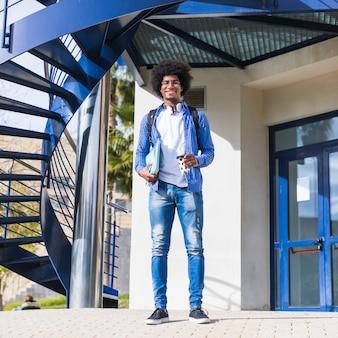 大学の建物の前に立っているアフロの若い男性学生の肖像画