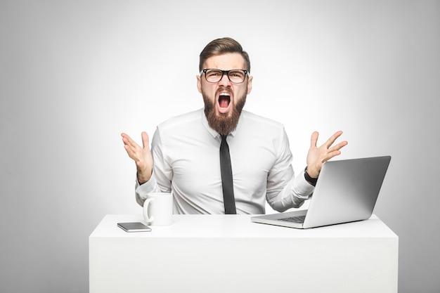흰 셔츠와 검은 넥타이를 한 공격적인 사업가의 초상화가 사무실에 앉아 팔을 들고 카메라를 보고 소리를 지르며 기분이 좋지 않습니다. 실내 스튜디오 촬영, 고립 된 회색 배경