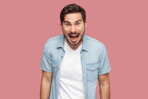 파란색 캐주얼 스타일 셔츠를 입고 화난 얼굴로 카메라를 보고 비명을 지르는 공격적인 충격을 받은 잘생긴 수염난 청년의 초상화. 실내 스튜디오 촬영, 분홍색 배경에 격리.