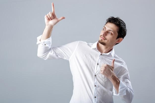 Портрет ahandsom улыбается брюнет мужчина в рубашке, показывая большие пальцы руки