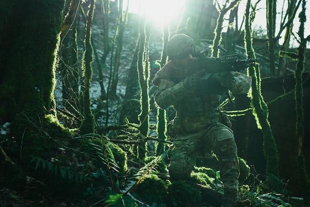 Портрет страйкбола в профессиональном оборудовании в шлеме, направленном на жертву с ружьем в лесу. солдат с оружием на войне