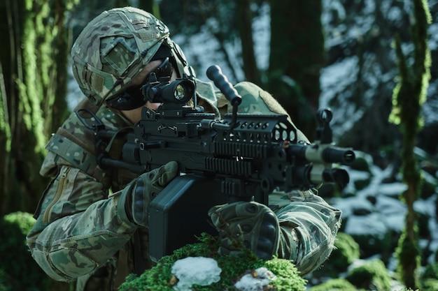 숲에서 총을 가진 피해자를 목표로 헬멧에 전문 장비에 airsoft 선수의 초상화. 전쟁에서 무기와 군인
