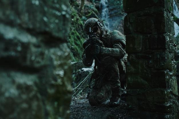 森の中で銃を持った犠牲者を目指してヘルメットのプロの機器でエアガンプレーヤーの肖像画。戦争で武器を持った兵士