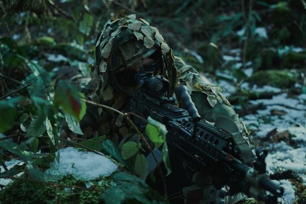 숲에서 총으로 피해자를 목표로 헬멧에 전문 장비에서 airsoft 선수의 초상화. 전쟁에서 무기를 든 군인