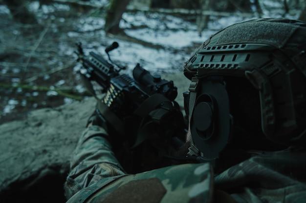 Портрет страйкболиста в профессиональном оборудовании в шлеме, направленного на жертву с ружьем в лесу. солдат с оружием на войне