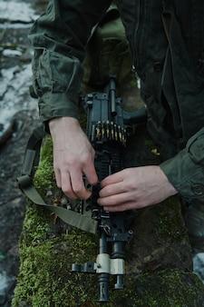 プロの装備のエアガンプレーヤーの肖像画は、森の中で弾丸で銃をロードします。戦争で武器を持った兵士