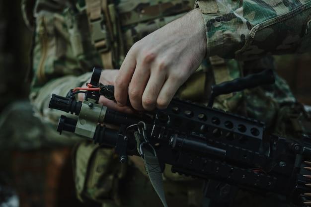 전문 장비를 입은 에어소프트 선수의 초상화는 숲에서 총알이 든 총을 장전합니다. 전쟁에서 무기를 든 군인