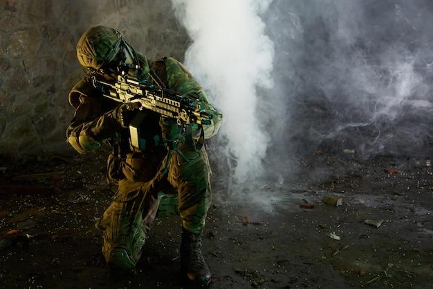 버려진 폐허가 된 건물에 기관총이 달린 전문 장비를 갖춘 에어소프트 선수의 초상화. 연기와 안개 속에서 전쟁에서 무기를 든 군인