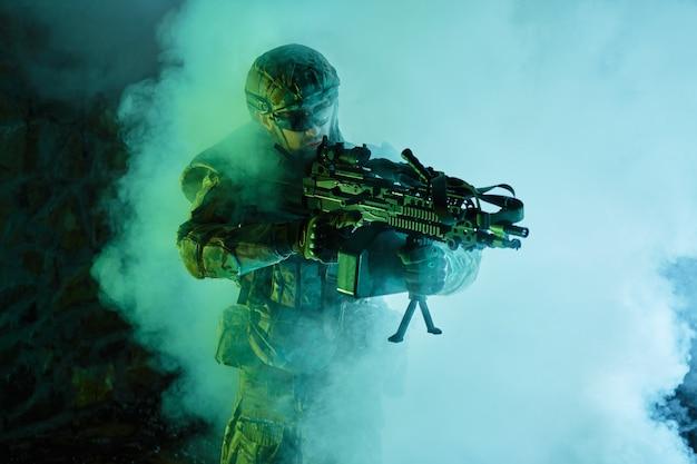 Портрет страйкбола в профессиональном снаряжении с пулеметом в заброшенном разрушенном здании. солдат с оружием на войне в дыму и тумане