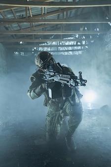 버려진 폐허가 된 건물에 기관총이 달린 전문 장비를 갖춘 에어소프트 선수의 초상화. 전쟁에서 무기를 든 군인