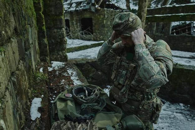 森の中で機関銃を備えたプロの機器でエアガンプレーヤーの肖像画。戦争で武器を持った兵士